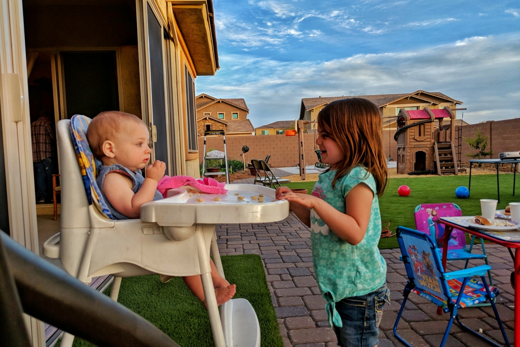 Baby girl in a high chair talking to her older sister