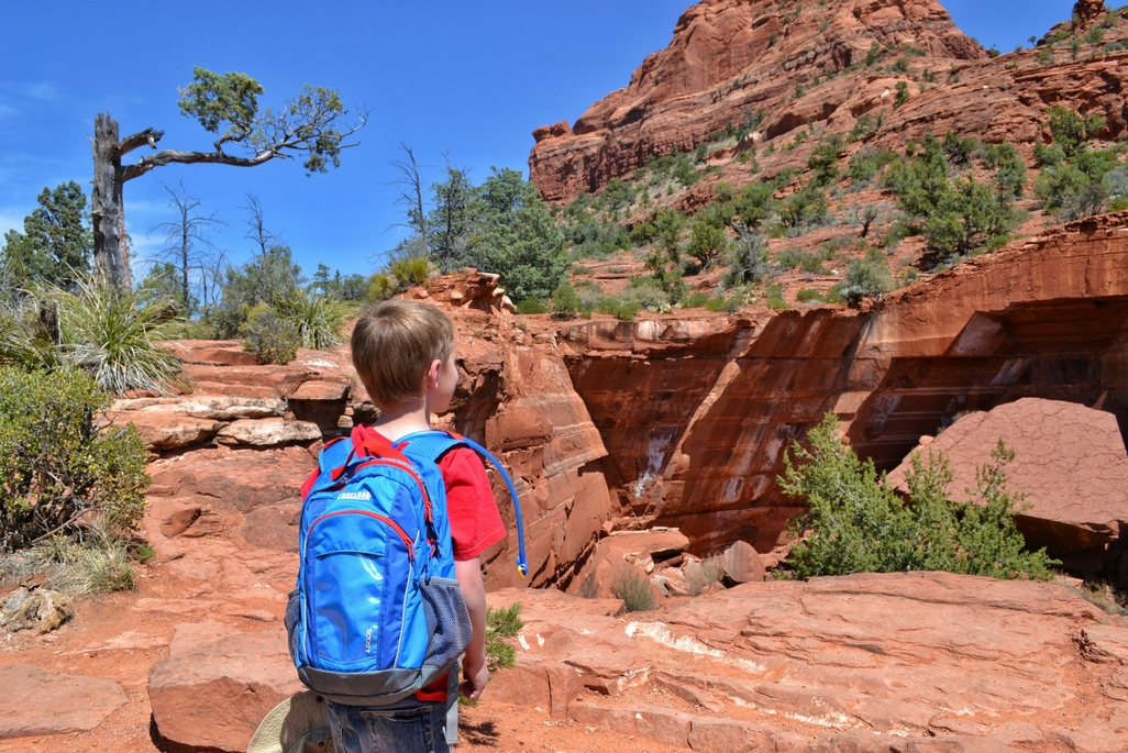 Young boy with blue backpack at Devil's Kitchen in Sedona Arizona
