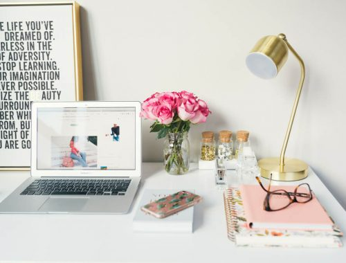 laptop on desk, flowers, cell phone, glasses