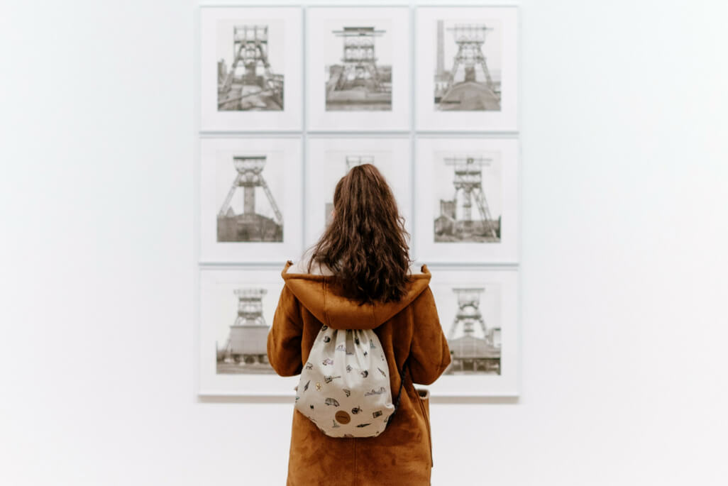 woman staring at drawings at an art gallery