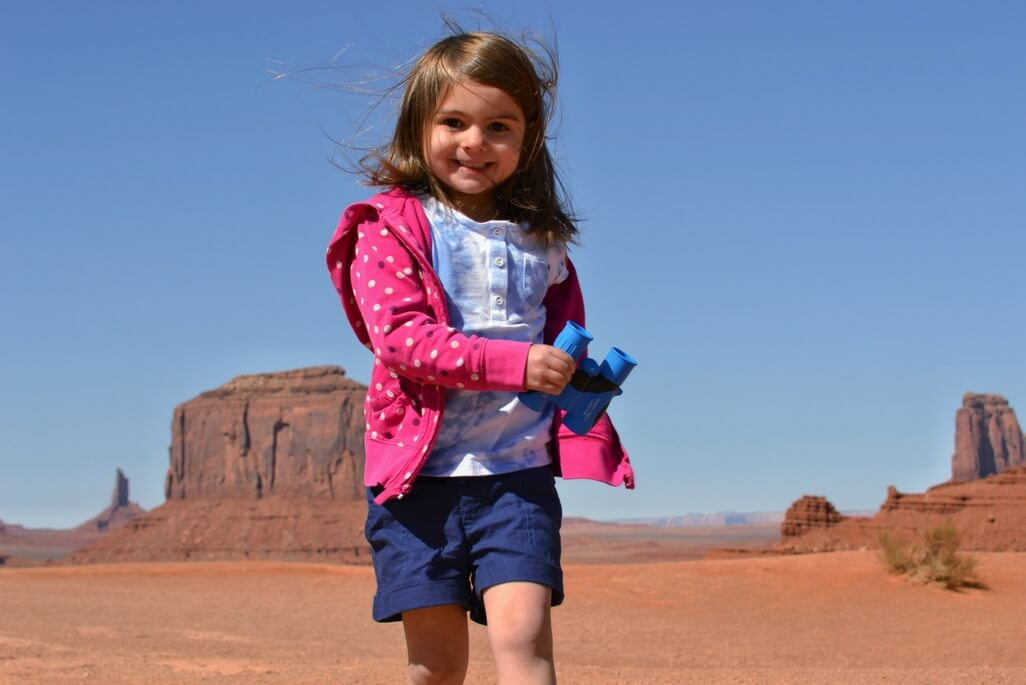 Girl with blue binoculars at Monument Valley
