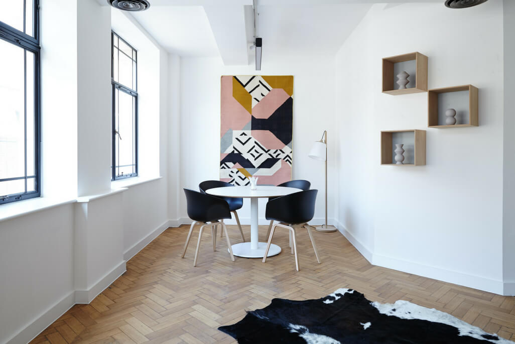 white dining table with black chairs in front of large painting