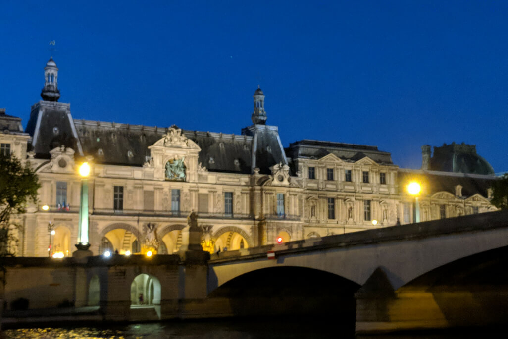 A Weekend in Paris: View of the Louvre at night from a Seine River Cruise in Paris, France