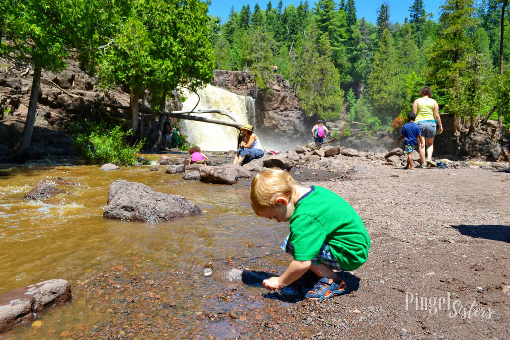 little boy exploring a the base of Gooseberry Falls in Minnesota