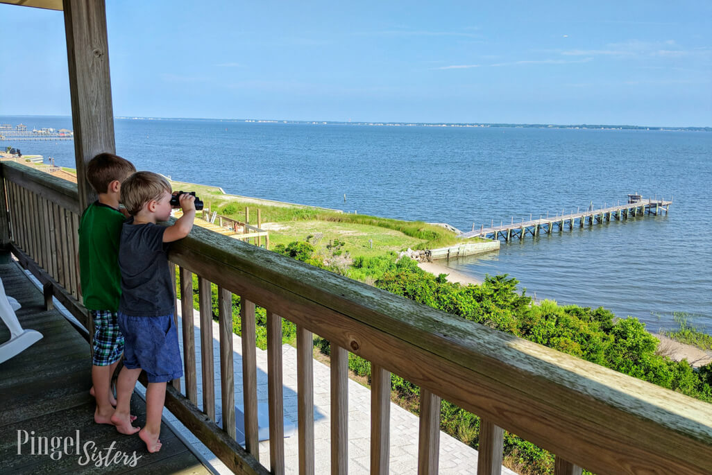 Two boys looking through binoculars at Bogue Sound