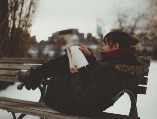 woman reading on park bench