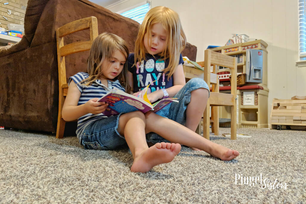 two little girls reading a book together