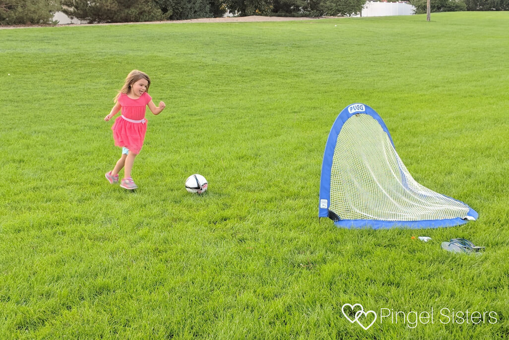 Little girl in pink dress scoring a goal in soccer