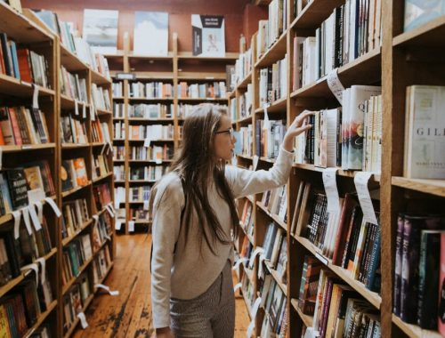 woman browsing bookshelves at bookstore