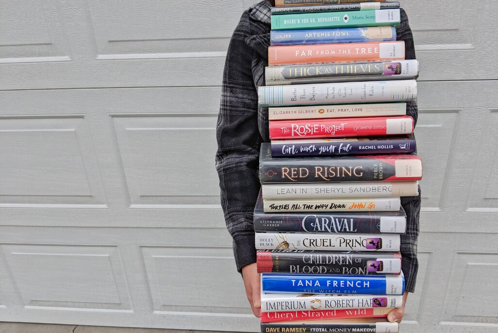 Rachael holding a gigantic stack of books