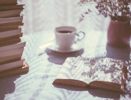 memoirs that will make you cry, open book, cup tea, bookstack