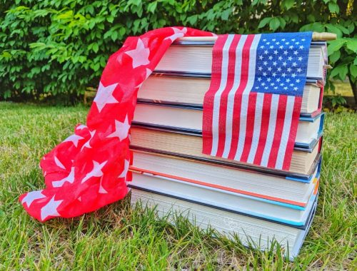american flag, book stack, red scarf with white stars